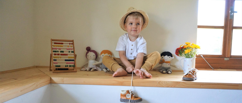 chlapeček sedí mezi látkovými panenkai a drží botu